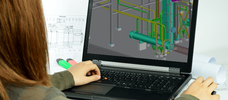 looking over a womans shoulder as she works on 3D piping designs on a CAD Program